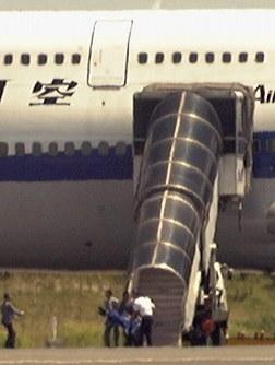<全日空機乗っ取り事件>1999年7月23日、羽田空港を離陸した全日空ジャンボ機で、包丁を持つ男が操縦室に押し入り、長島直之機長(51)を刺殺した。男は操縦かんを握って機体を急降下させるなど異常な行動を続け、約500人の乗客らが大惨事に巻き込まれる危険にさらされた。写真は羽田空港で全日空機から連れ出される男=羽田空港で23日午後0時35分、藤井太郎撮影