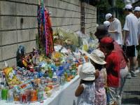<長崎幼児誘拐殺人事件>2003年7月1日、長崎市で4歳の男児が誘拐され、8階建て立体駐車場の屋上から突き落とされ死亡した。長崎県警は殺害を認めた中学1年の男子生徒(12)を補導。家裁は児童自立支援施設へ送致する保護処分を決定した。事件現場近くに設けられた祭壇には1カ月たっても、たくさんの供え物が並んだ=長崎市で2003年8月3日午前11時35分、横田信行撮影