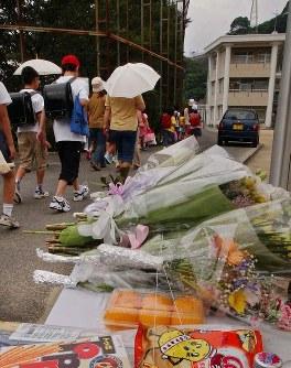 <小6同級生殺害事件>2004年6月1日、長崎県佐世保市の小学校で、小学6年の女児(12)が同級生の女児(11)にカッターナイフで切られ死亡した。加害女児は児童自立支援施設送致の保護処分に。前年に続いて起きた低年齢による凶悪事件に衝撃が広がった。写真は花束や菓子類が供えられた献花台の横を登校する児童=長崎県佐世保市で2004年6月7日午前7時48分、金澤稔撮影