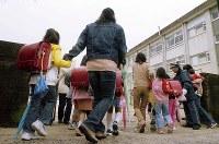 <奈良小1女児殺害事件>2004年11月17日、奈良市の小学1年の女児(7)が下校中に行方不明になり、道路脇の側溝で遺体が見つかった。殺人やわいせつ目的誘拐の罪などに問われた小林薫元死刑囚(13年2月執行)に対して奈良地裁は「極めて残忍」と指弾した。写真は事件後、現場の近くの小学校で母親に連れられて登校する児童たち=奈良市で2004年11月19日午前8時9分、貝塚太一撮影
