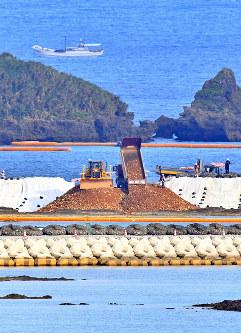 辺野古沿岸部の埋め立て海域で、ダンプカーから次々と投入される土砂=沖縄県名護市で2018年12月14日午後3時35分、野田武撮影