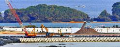 辺野古沿岸部の埋め立て海域で、ダンプカーから次々と投入される土砂(右)=沖縄県名護市で2018年12月14日午後2時28分、野田武撮影