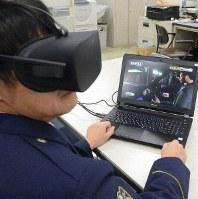 再生ゴーグルをかけてVRを体験する福岡県警の警察官。パソコンのモニターには警察官が見ている同乗者目線の映像が映し出されている=福岡市博多区の県警本部で2018年12月13日、宮崎隆撮影
