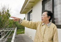 Yoshie Higa points toward U.S. Marine Corps' Camp Schwab from her home in the Abu district of the Okinawa Prefecture city of Nago, on Dec. 12, 2018. Visible beyond the base is the area zoned off for land reclamation for a replacement base for U.S. Marine Corps Air Station Futenma in the southern Okinawa prefectural city of Ginowan. (Mainichi/Tadashi Sano)
