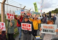 Protesters oppose the start of land reclamation for the construction of a replacement military base for U.S. Marine Corps Air Station Futenma in front of the gates of the U.S. Marine Corps' Camp Schwab in the Henoko district of Nago, Okinawa Prefecture, at around 7:30 a.m. on Dec. 14, 2018. The Okinawa Defense Bureau began dumping soil and sand into the water some 3 1/2 hours later. (Mainichi/Takeshi Noda)