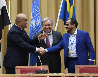 Head of delegation for rebel forces known as Houthis, Mohammed Abdulsalam, right, and Yemen Foreign Minister Khaled al-Yaman, left, shake hands together with U.N. Secretary-General Antonio Guterres, during the Yemen peace talks closing press conference at the Johannesberg castle in Rimbo, Sweden, on Dec. 13, 2018. (Pontus Lundahl/TT News agency via AP)