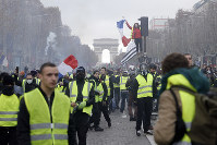 In this Nov. 24, 2018 file photo, demonstrators march on the famed Champs-Elysees avenue in Paris, France. (AP Photo/Kamil Zihnioglu)