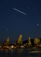 A bright meteor from the Geminid meteor shower flies through the sky above the natural scenic site