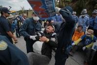 米軍普天間飛行場移設のための工事が進むキャンプシュワブのゲート前で、座り込んで埋め立てに抗議の声を上げるなか、排除しようとする警察官に担がれる男性=沖縄県名護市で2018年12月13日午後12時2分、和田大典撮影