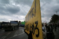 米軍普天間飛行場移設のための工事が進むキャンプシュワブのゲート前で、座り込んで埋め立てに抗議の声を上げる人たち=沖縄県名護市で2018年12月13日午後12時14分、和田大典撮影