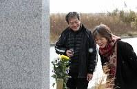 慰霊碑の前で「温かいコーヒー持ってきたよ」と行方不明の娘真希さんに語りかける大久保三夫さん(左)と妻恵子さん=宮城県山元町で2018年12月9日、佐々木順一撮影