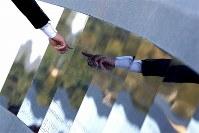 町の慰霊碑の除幕式終了後、慰霊碑の前では家族の名前を探したり、友人らの名前を見つけて思い出を語る人たちの姿が見られた=宮城県女川町で2018年10月1日、佐々木順一撮影