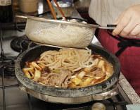 牛肉を半分取り出し、ネギを戻して絡め、だし汁を加える。サッとゆでてほぐしたうどんを入れる=尾籠章裕撮影