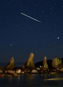 A bright meteor from the Geminid meteor shower is seen in the sky above the natural scenic site of