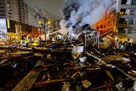 消火活動を続ける消防隊員ら。周辺には建物の残骸が散乱していた=札幌市豊平区で2018年12月16日午後9時25分、貝塚太一撮影