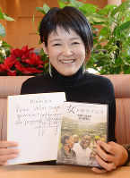 「コンゴ女性のために志を共にしてくれてありがとう」と書かれたムクウェゲ氏の色紙とドキュメンタリー映画のDVDを持つ大平和希子さん=富山市で、鶴見泰寿撮影