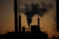 Smoke billows from a chimney of the Solvay factory for production and processing of plastic materials, in Ospiate, near Milan, Italy, Friday, Dec. 14, 2018. (AP Photo/Luca Bruno)