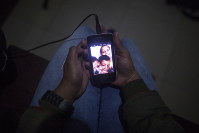 n this Dec. 11, 2018 photo, Emili Espinoza holds her cell phone as she makes an international video call to her children from the room she shares with other migrants in Bogota, Colombia. Through the fuzzy, at times pixilated connection, Espinoza gets glimmers of hope that the separation will not cast a permanent scar on her children. (AP Photo/Ivan Valencia)