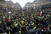 Demonstrators gather during a protest outside the Opera house, Saturday, Dec. 15, 2018 in Paris. (AP Photo/Michel Euler)