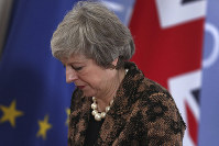 British Prime Minister Theresa May walks by the Union flag and the EU flag as she departs a media conference at an EU summit in Brussels, Friday, Dec. 14, 2018.  (AP Photo/Francisco Seco)