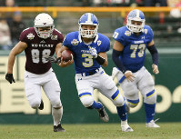 Kwansei Gakuin quarterback Kosei Okuno (3) goes on the attack during his American football team's 37-20 victory over Tokyo's Waseda University in the Koshien Bowl. (Kyodo)