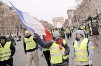 黄色いベストを着てシャンゼリゼ通りを練り歩く人々=フランス首都パリで15日、AP