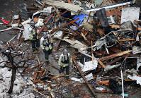 爆発から一夜明け、現場周辺を調べる消防隊員ら=札幌市豊平区で2018年12月17日午前9時28分、貝塚太一撮影