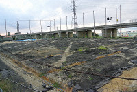 The soccer field built on land returned from Kadena Air Base where metallic barrels contaminated with dioxins were discovered and where surveys to detect other pollutants are still ongoing is seen on Nov. 14, 2013. Background, left, is where the barrels were found. The base, in the background, right, spans the towns of Chatan and Kadena, and the city of Okinawa, in Okinawa Prefecture. (Mainichi/Satoshi Kusakabe)