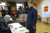 Oleg Kozhemyako, acting governor of the far eastern region of Primorsky Krai stands as he waits to get his ballot at a polling station in Vladivostok, Russia, on Dec. 16, 2018. (Igor Novikov, Governor and Administration of Primorye Territory press service via AP)