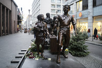 People pass a commemorative memorial statue to perpetuating the memory of the 'Kindertransport' (children transport) near Friedrichstrasse train station in central in Berlin, Germany, on Dec. 17, 2018. (AP Photo/Markus Schreiber)