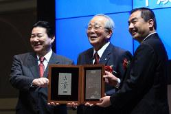 JALが再上場。通知書を手に笑顔の稲盛和夫名誉会長(中央)=2012年