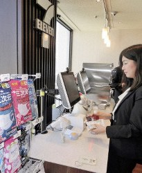 An NEC Corp. employee makes an automated payment after a small camera at a checkout counter recognizes her face in Tokyo's Minato Ward, on Dec. 17, 2018. (Mainichi/Akane Imamura)