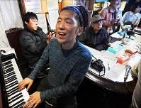 ジャズ喫茶「ブルーノート」での最後のセッションをするジャズピアニストの石井彰さん(左から2人目)と演奏に聴き入るマスターの菅原乙充さん(同3人目)=大阪府豊中市で2018年12月12日、山崎一輝撮影