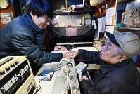 ジャズ喫茶「ブルーノート」での最後のセッションに集まった男性と握手をするマスターの菅原乙充さん(右)=大阪府豊中市で2018年12月12日、山崎一輝撮影