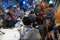 ジャズ喫茶「ブルーノート」での最後のセッションに聴き入るマスターの菅原乙充さん(左端)=大阪府豊中市で2018年12月12日、山崎一輝撮影