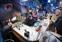 ジャズ喫茶「ブルーノート」での最後のセッションが終わり、ジャズピアニストの石井彰さん(左端)たちから拍手を送られるマスターの菅原乙充さん(中央)=大阪府豊中市で2018年12月12日、山崎一輝撮影