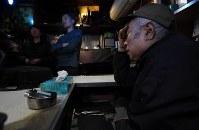 ジャズ喫茶「ブルーノート」での最後のセッションに集まったジャズピアニストの石井彰さん(右から2人目)らの前で涙を流すマスターの菅原乙充さん(右端)=大阪府豊中市で2018年12月12日、山崎一輝撮影