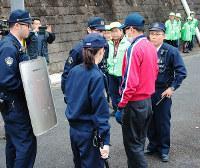 防犯訓練で窃盗犯役を問い詰める警察官と、見守る地元自治会防犯隊員たち=奈良県大淀町で、栗栖健撮影