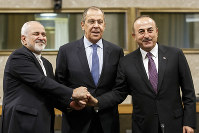 Iranian Foreign Minister Mohammad Javad Zarif, left, Russian Foreign Minister Sergei Lavrov, center, and Turkish Foreign Minister Mevlut Cavusoglu shakes hands after a joint statement following the consultations on Syria, at the European headquarters of the United Nations in Geneva, Switzerland, on Dec. 18, 2018.. (Salvatore Di Nolfi/Keystone via AP)