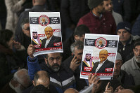 In this Nov. 16, 2018 file photo, members of Arab-Turkish Media Association and friends of Washington Post columnist Jamal Khashoggi hold posters showing images of Saudi Crown Prince Muhammed bin Salman and of Khashoggi, as they attend funeral prayers in absentia for him following his killing the previous month in the Saudi Arabia consulate, in Istanbul. (AP Photo/Emrah Gurel)