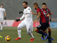 Milan's Gonzalo Higuain, left, and Bologna's Larangeira Danilo vie for the ball during the Italian Serie A soccer match between Bologna and Milan at
