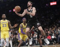 Brooklyn Nets' Joe Harris (12) drives past Los Angeles Lakers' LeBron James (23) during the second half of an NBA basketball game on Dec. 18, 2018, in New York. The Nets won 115-110. (AP Photo/Frank Franklin II)