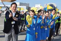 イベントで那覇行きの飛行機を見送るため、旗を振る井上慎一社長(左端)と笑顔の客室乗務員ら=成田空港で中村宰和撮影