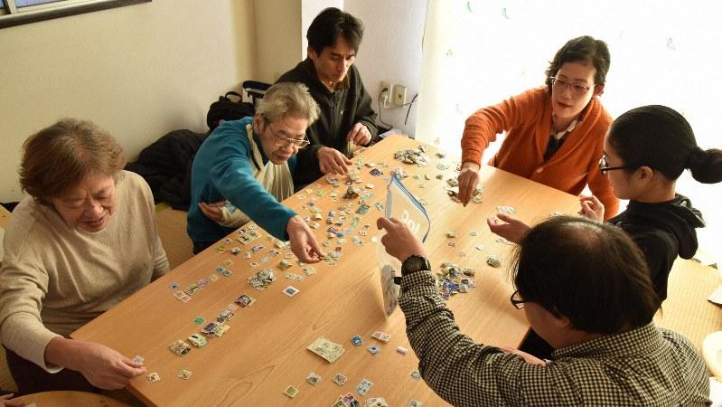 「キーベース」で使用済み切手の仕分けをする今宮眞幸さん(左から2人目)=筆者撮影