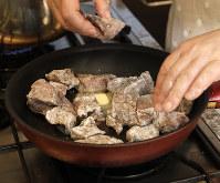 フライパンにオリーブ油とバターを熱し、牛肉の表面を焼く=尾籠章裕撮影