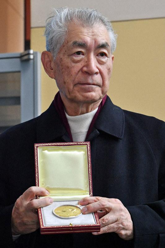 ノーベル賞授賞式から帰国し、報道陣にノメダルを披露する本庶佑・京都大特別教授=関西国際空港で2018年12月14日