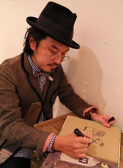 絵本「ゴリラのくつや」にサインとイラストを描く著者の谷口智則さん=東京都中央区の森岡書店で2018年12月16日、長谷川直亮撮影