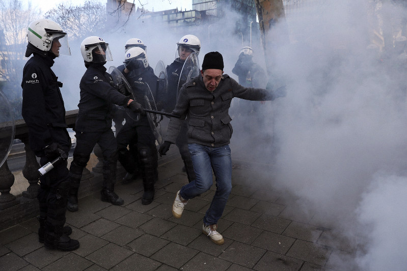 A protester is pushed by anti riot police officers during a demonstration in Brussels Saturday Dec. 22 2018