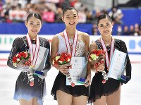 Winner Kaori Sakamoto, center, runner-up Rika Kihira, left, and third-placed Satoko Miyahara, pose for a commemorative photograph on the podium at Japan's national figure skating championships at Towa Pharmaceutical Co.'s Ractab Dome in the city of Kadoma, Osaka Prefecture, on Dec. 23, 2018. (Mainichi/Kenji Ikai)
