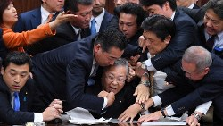 参院法務委員会の入管法改正案採決で横山信一委員長(中央)に詰め寄る議員ら=国会内で2018年12月8日、渡部直樹撮影
